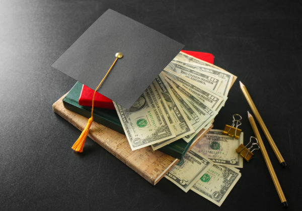 graduation hat on top of money and books