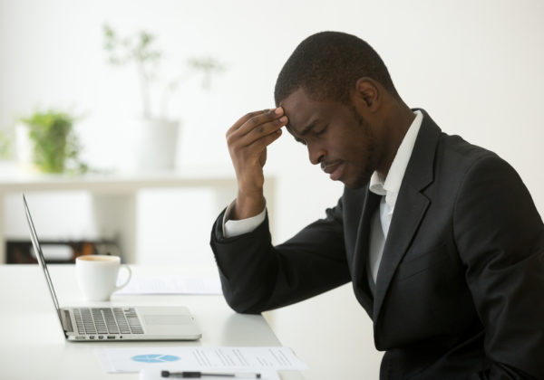 frustrated african american business man working on a laptop