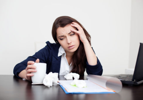frustrated woman with coffee and crumpled paper