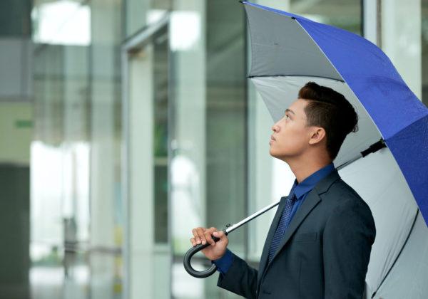 man in suit with blue umbrella