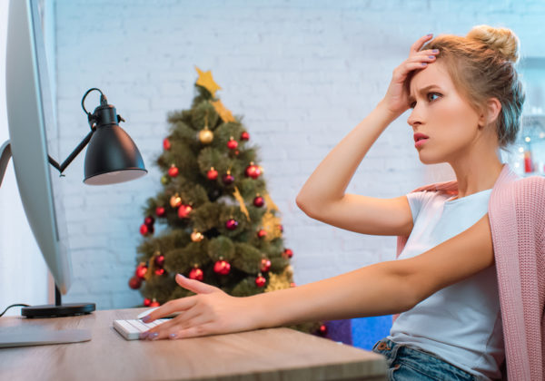 frustrated woman at desk in front of christmas tree