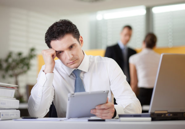 frustrated man working at his desk on a tablet