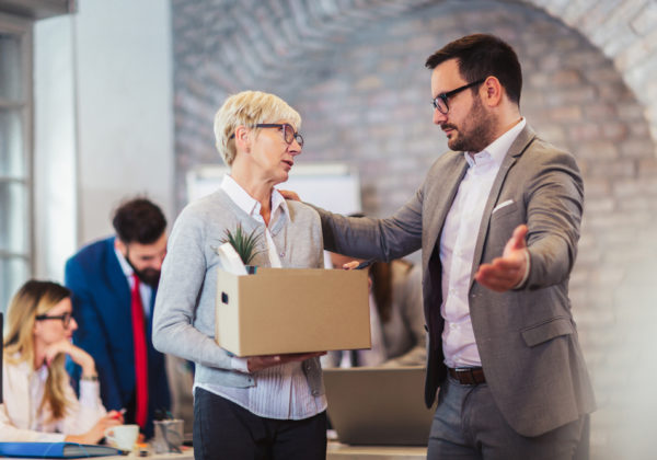 woman holding her things fired by male boss