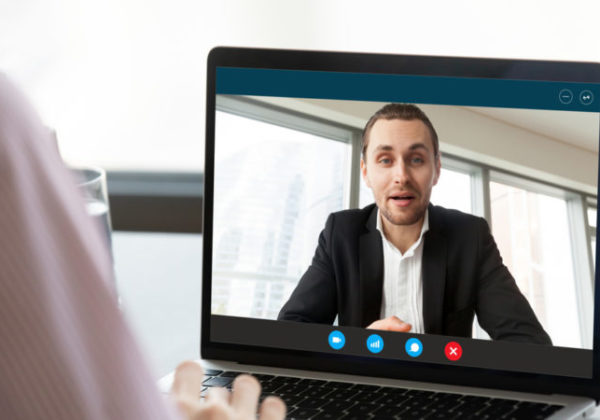 Businesswoman having distant talk with colleague through videocall screen view