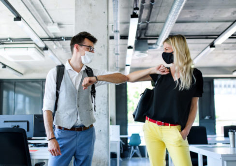 Young people with face masks back at work in office after lockdown, greeting.
